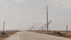 Broken and leaning power poles along flooded road in the wake of a hurricane - stock footage