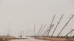 Vehicle approaching on a flooded road beside leaning power poles - stock footage