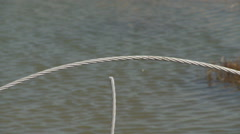 Broken and twisted power cable along a washed-out road near a beach Stock Footage