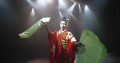 Beautiful Japanese geisha posing for the camera with fans on stage, epic slow Stock Footage