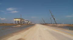 Road through beachfront neighborhood with receding flood waters and storm damage Stock Footage