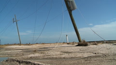 Tangled power lines on ground with tilt-up to broken lines dangling from leaning Stock Footage