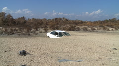Zoom-in to car almost buried in beach sand after a hurricane - stock footage