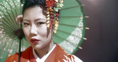 Beautiful Japanese geisha posing for the camera with an umbrella on stage, epic Stock Footage