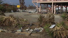 A wrecked stretch limo near a debris-covered area after a hurricane Stock Footage
