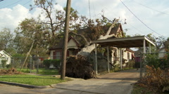 A large tree uprooted and lying on the roof of a residence after a hurricane Stock Footage