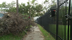 Broken branches and leaning fence along a residential sidewalk after a hurricane - stock footage