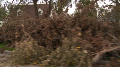 Curbside debris awaiting pick-up in a neighborhood cleaning up after a hurricane - stock footage
