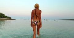 Woman entering into sea at Slatinica beach, Croatia Stock Footage