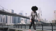 Female fitness model training outside in New York City with skyline and Brooklyn Stock Footage
