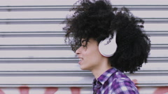 Portrait of pretty Afro American Female on street looking listening to music on - stock footage