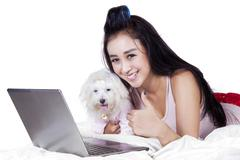 Cute girl with dog showing thumb up - stock photo
