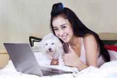 Female model with dog and notebook on bed - stock photo