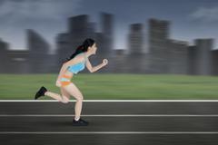 Stock Photo of Female runner running on a track