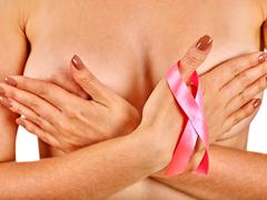 Pink badge on woman finger to support breast cancer cause Stock Photos