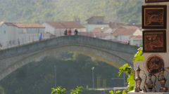 View of traditional souvenirs and people walking on Stari Most in Mostar Stock Footage