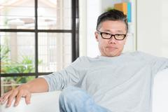 Stock Photo of Mature 50s Asian man sitting at home.