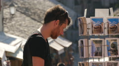 View of a man looking at postcards in Mostar Stock Footage