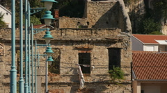 View of blue lamp posts and a ruined building in Mostar Stock Footage