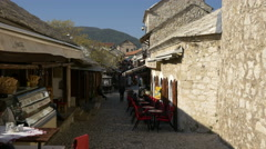 Stock Video Footage of View of Lasta pub and Stari Most restaurant on a narrow street in Mostar