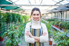 Beautiful happy young woman gardener in colorful striped apron Stock Photos