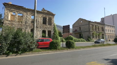 Stock Video Footage of Driving by two stone buildings in Mostar, Bosnia-Herzegovina