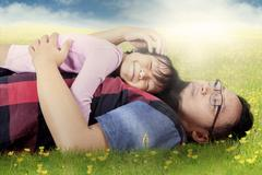 Man caress his daughter on meadow - stock photo