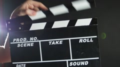 Hands holding a film clapper board, on black, close up, back light Stock Footage