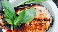 Grilling salmon on grid over barbecue Stock Footage