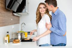 Beautiful wife making pancakes and flirting with husband Stock Photos