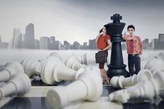 Two entrepreneurs standing on the chessboard - stock photo