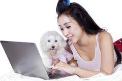 Woman and dog use laptop on bed - stock photo