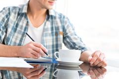 Pensive man drawing and drinking coffee in office - stock photo