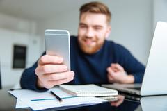 Man sitting at the table and using smartphone Stock Photos