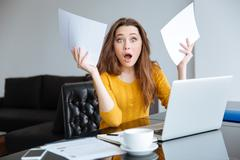 Amazed woman sitting at the table with bills Stock Photos