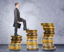 Businessman walking on stack of coins Stock Photos