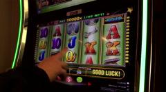 Close up man playing slot machine inside Hard Rock Casino - stock footage