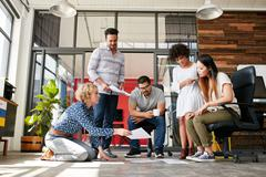 Designers planning layout on floor of office Stock Photos