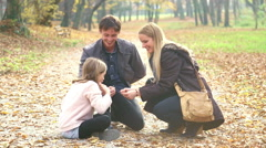 Parents having fun with daughter playing games in the park - stock footage