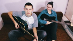 Creative happy couple playing guitar - stock footage