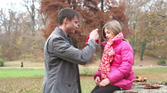 Father putting red cap on daughter's head - stock footage