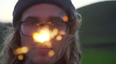 Slow Motion Young Man Staring At Sparkler At Sunset - stock footage