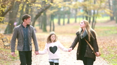 Family walking in the park, father takes daughter in his arms Stock Footage