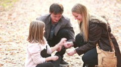 Young family sitting on pathway in park and playing games - stock footage