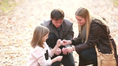 Young family sitting on pathway and playing games Stock Footage