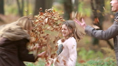 Girl throwing leaves on her parents Stock Footage