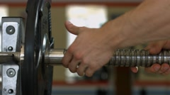 Barbells hanging on metal rack in gym hall. - stock footage