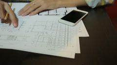 Woman architect working with blueprint sheets, layouts and drawings of the - stock footage