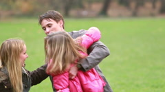 Young parents playing with daughter in park Stock Footage