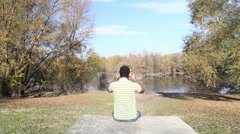 Man listening to music using headphones while sitting by lake Stock Footage